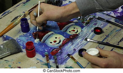 Artist paint a New Year painting of snowmen with acrylic