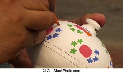 Artist painting a paper mache powder box - Close up of an...