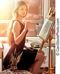 Artist painting on easel in studio. Girl paints with brush.