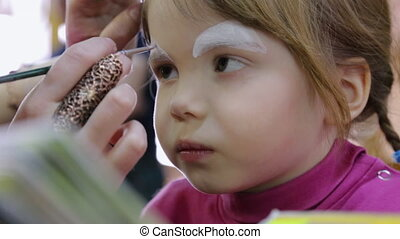 Artist painting on face of small girl