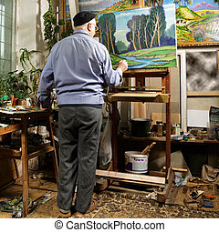 Artist painting picture in workshop rear view