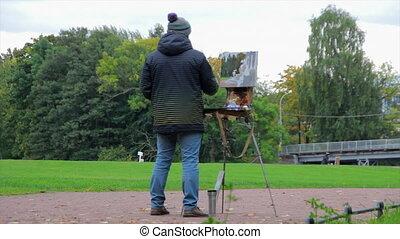 Artist paints in autumn Park