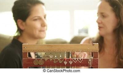 Artist presenting earrings to client - Shot of Artist...