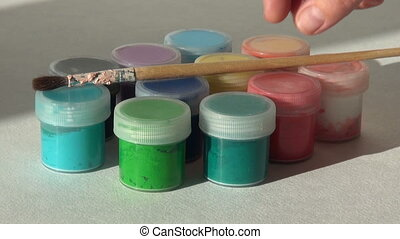 artist puts brush on the jars of Acrylic gouache paint....