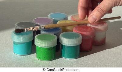 artist puts brush on the jars of Acrylic gouache paint....