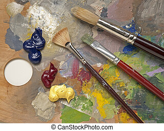 Artist supplies - paintbrushes and paint on multicolored ...