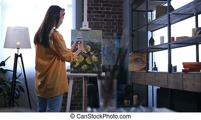 Artist taking photo of canvas with flowers - Back view of...