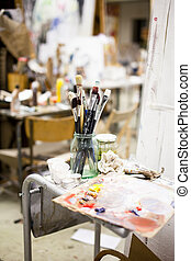 Artist tools in a jar of glass in a studio