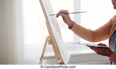 artist with palette and brush painting at home - art,...