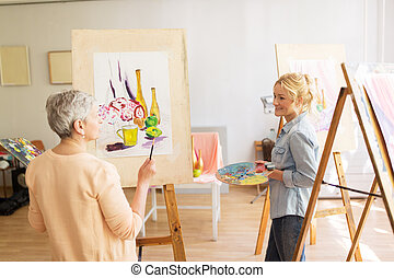 artist women with easels painting at art school - creativity...