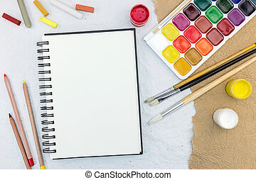 artist work tools on table: watercolor, paintbrushes and pencils with chalks
