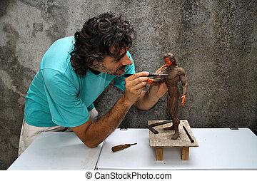 artist at work on a plasticine miniature of human body