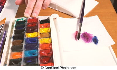 Artist working on painting with watercolor paint in light...