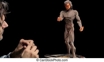 artist working on plasticine human muscolar figurine