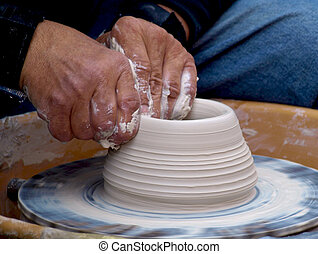 Close up of artist's hands creating pottery from clay.
