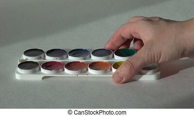 artist works with paint on the table. round watercolor...