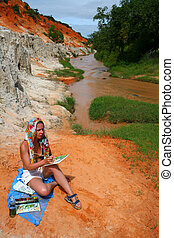 artist - young woman painting a picture near brown stream