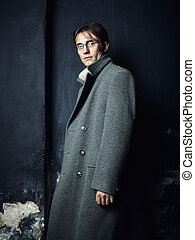 Artistic dark portrait of the young beautiful man in a gray coat. Close up