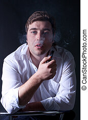 portrait of the young beautiful man smoking a pipe