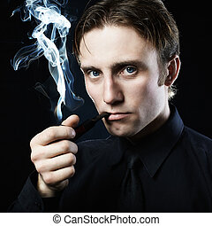 Artistic dark portrait of the young beautiful man. The young man smokes a tube. Close up