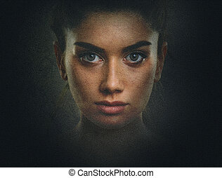 Artistic dark portrait of young woman with beautiful face and eyes