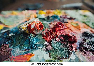 paint, brushes and knives on paint background