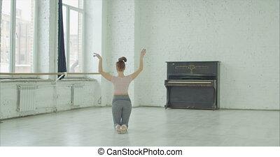 Artistic gymnast training short routines in studio -...
