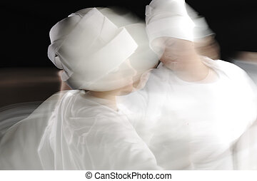 Artistic motion photo of white sufy female dancers