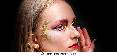 Artistic professional make up applies eye shadow.