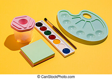 Artistic tools - brushes, watercolor paint, notebook