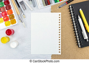 artistic work tools: watercolor, paintbrushes, chalks and sketchbook on desk