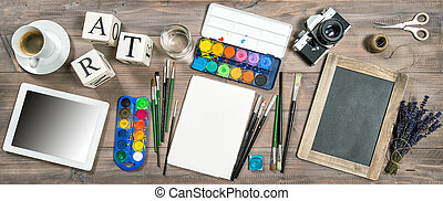 Artistic workplace mockup. Watercolor, brushes, digital tablet, vintage camera