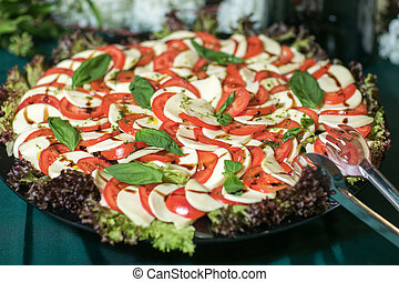 Artistically arranged cheese and tomato salad in alternating...