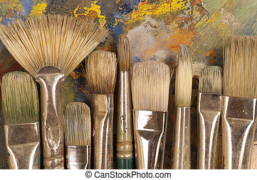 Close up of artist's brushes on an painting pallet.