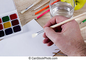 Artist's hand at work, paints, brushes and pencils