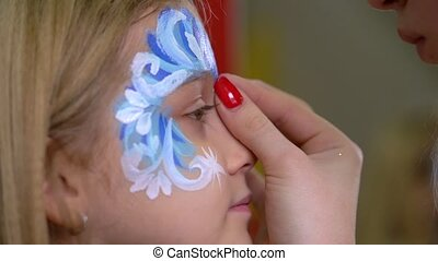 Artist's hand glueing rhinestones on the kid's face....