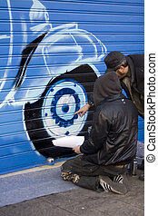 Artists painting a graffito on portcullis