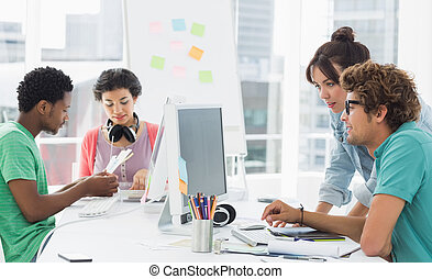 Artists working at desk in creative office