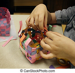 Arts and crafts with the hands of a child crafting a basket made of construction paper as a symbol of art education at schools or other creative activities for kids.