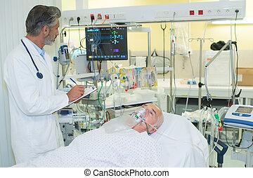 arts, naast, patiënt, met, zuurstofmasker, het liggen op het bed