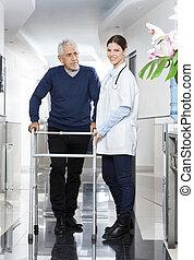 arts, staand, met, hogere mens, gebruik, walker, in, rehab, centrum