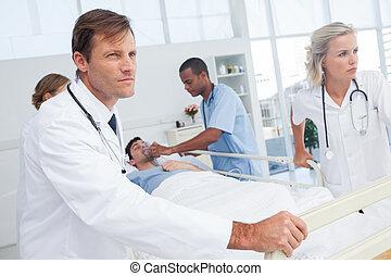 artsen, voortvarend, de, bed, van, een, patiënt