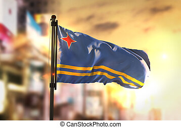 Aruba Flag Against City Blurred Background At Sunrise Backlight