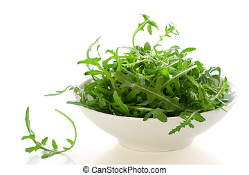 bowl of arugula leaves on white background
