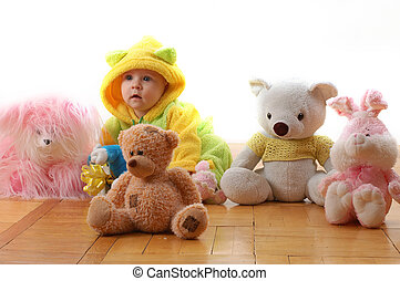 as a toy - a baby sittig between toys and looking like one...