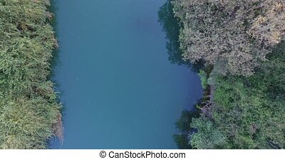 Ascending from river. Aerial footage of riverbank.