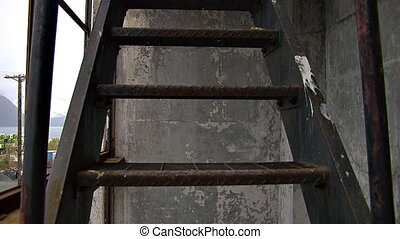 Climbing up the outer fire escape stairs of the spooky old Buckner Building in Whittier, Alaska and looking in through broken window to a room of decay, ruin, and graffiti.