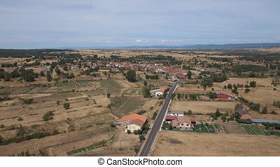 Ascending over vintage village in the plain, Spain -...