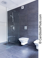 Luxurious grey bathroom with large granite tiles on the floor and walls, and glass shower screen