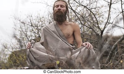 Ascetic yogi meditating in mountains